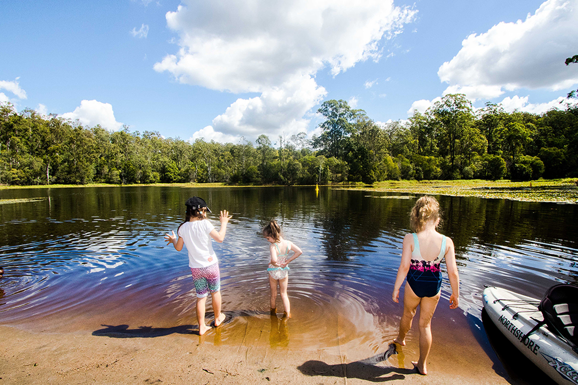 Three children in bathers tiptoe into the shallows of the reservoir against a backdrop of fringing forest and simmering water.