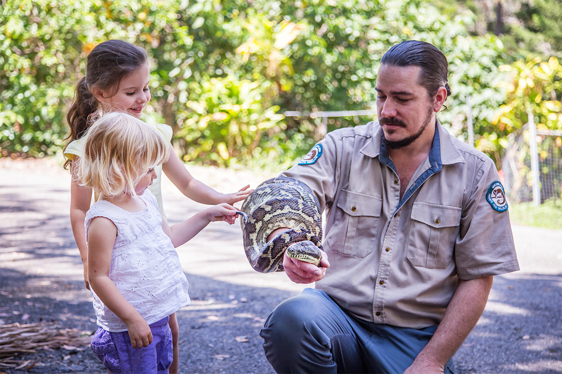 Two young girls pat a python coiled around a ranger's arm.
