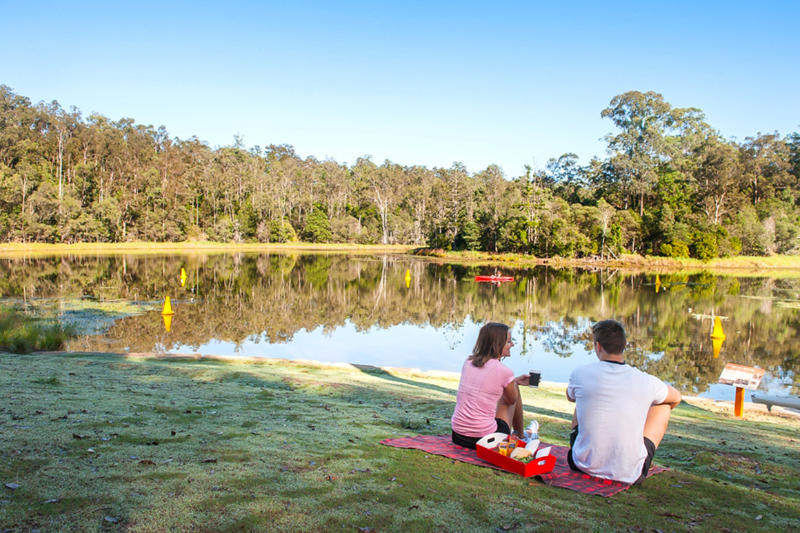 A couple sit on a picnic rug on the lawn overlooking the reservoir, with a red picnic hamper with wraps, sandwiches, juices and coffees.