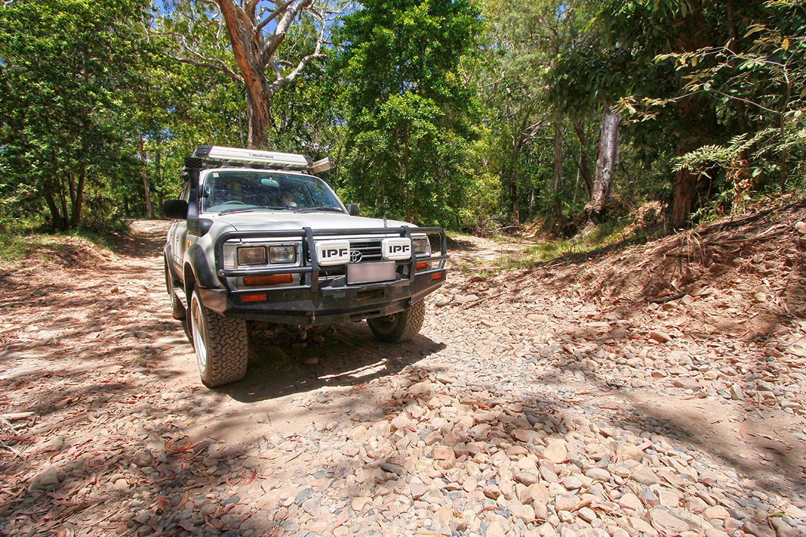 4WD vehicle driving on a sandy and rocky track with forest in background.