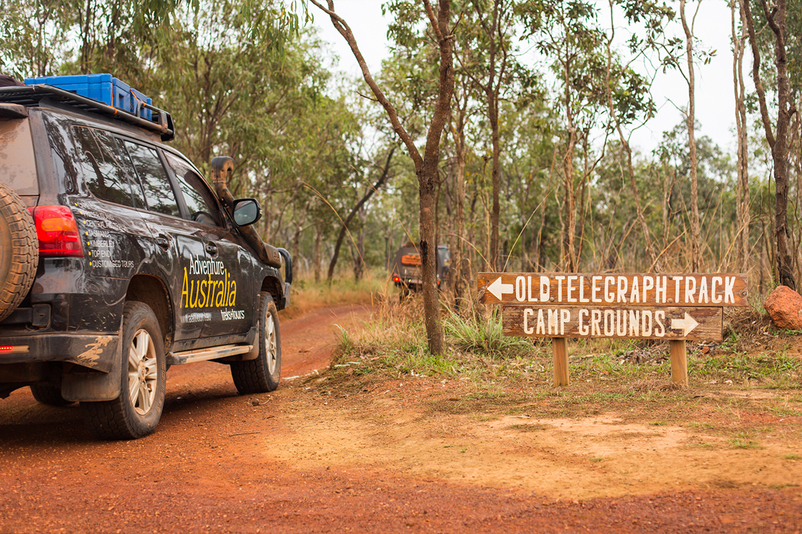 4WD vehicles follow a red dirt track surrounded by woodland and a hand-painted sign indicates the 'Old Telegraph Track'.