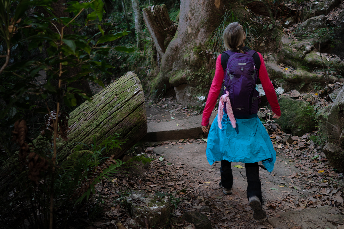 Hiker wears warm gear and pack on her back while walking on a rainforest track.