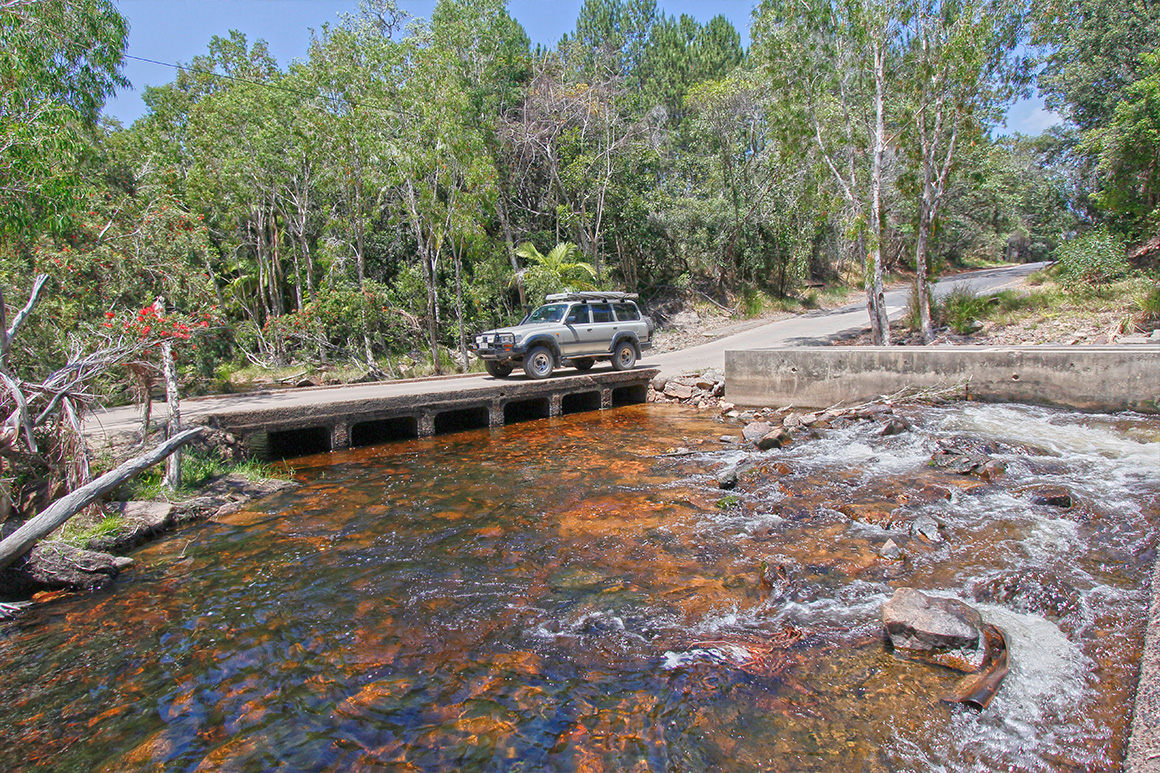 A vehicle crosses a low bridge over a creek on a paved road with forest in the background.
