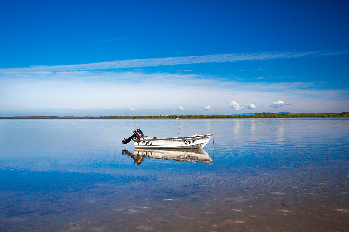 A small white tinnie rests at anchor in shallow water that reflects blue skies above, with distant forested shoreline and mountains in the background.